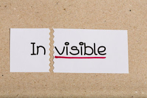 Two pieces of white paper with the word invisible turned into visible